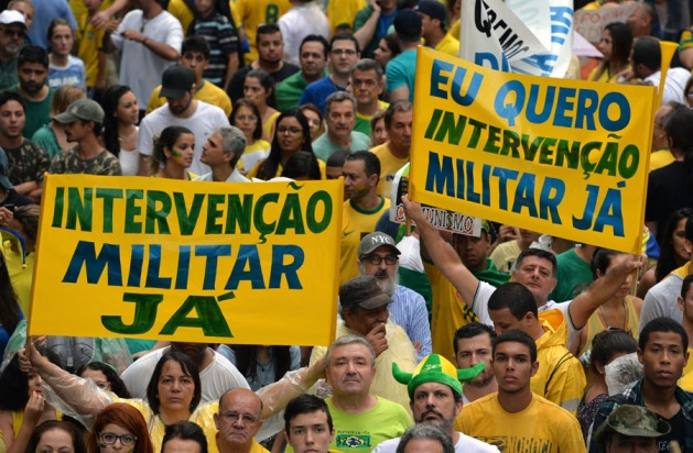 "Demonstrators hold signs reading ""Military intervention now"" as they rally to protest against the government of president Dilma Rousseff in Paulista Avenue in Sao Paulo Brazil on 15 March 2015. Tens of thousands of Brazilians turned out for demonstrations to oppose leftist president Dilma Rousseff, a target of rising discontent amid a faltering economy and a massive corruption scandal at state oil giant Petrobras. AFP PHOTO / NELSON ALMEIDA"